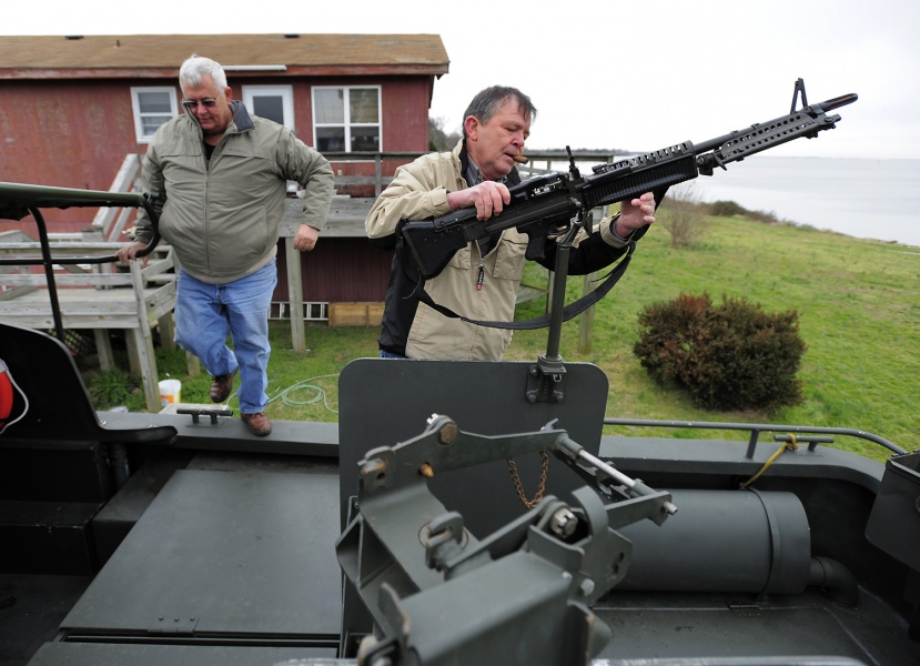 Dennis Ambruso (left) climbs aboard as Pat Doyle mounts a replica M-60 machine gun at the stern of Ambruso's fully restored Vietnam-era PBR 721 boat.