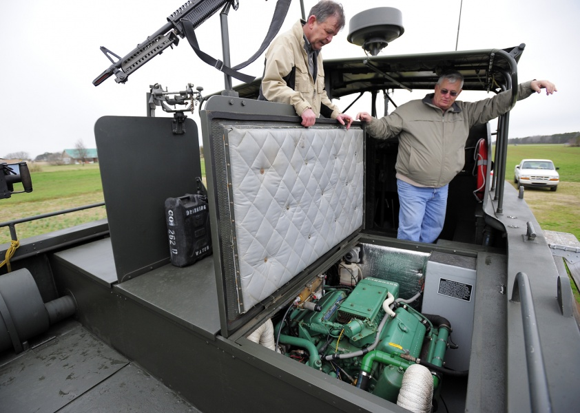 Dennis Ambruso (right) and Pat Doyle stand near the front gunner's rig of Ambruso's fully restored PBR 721 boat he brought down from Connecticut in his move to Currituck. The boat includes replica .50 caliber machine guns, a grenade launcher and an M-60 machine gun.